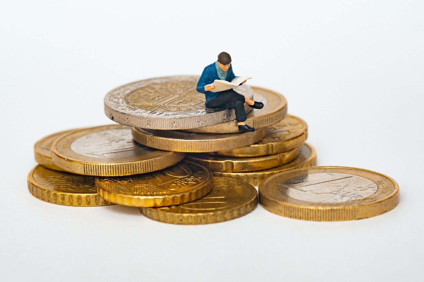 Osoba siedząca na stosie monet